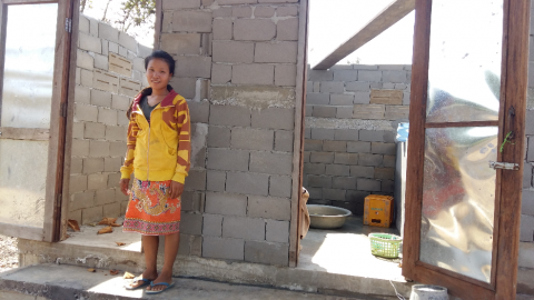 Mrs. Tan's daughter standing in front of new latrine